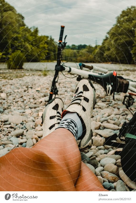 Young man takes a break with his MTB mtb Mountain bike Beach Isar River Nature Sportsperson Legs Athlete Bicycle ride a bike recover Exterior shot Cycling