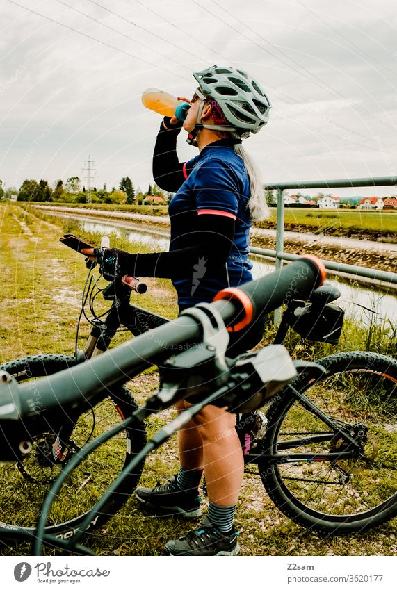 Young woman drinking from a bicycle bottle while mountain biking Mountain bike Bicycle Sports Athletic Athlete fun Helmet Jersey Exterior shot Fitness Cycling