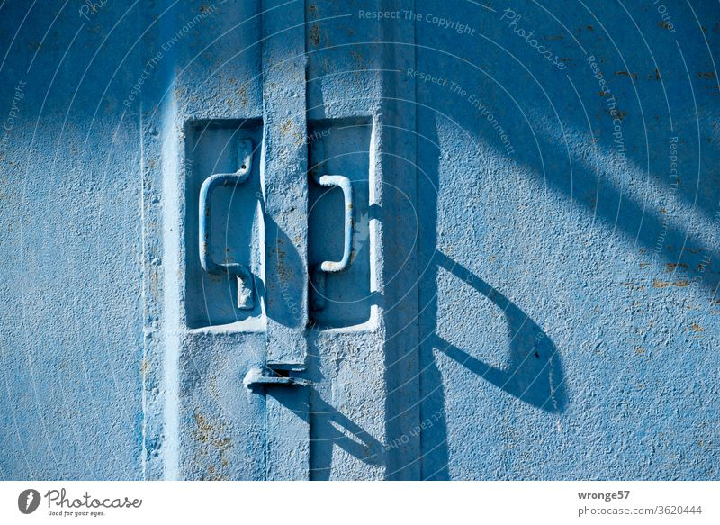 Close-up of two handles on a blue steel gate Shadow play shadow cast long shadows Goal Blue Garag Garage door Exterior shot Colour photo Deserted Day Closed