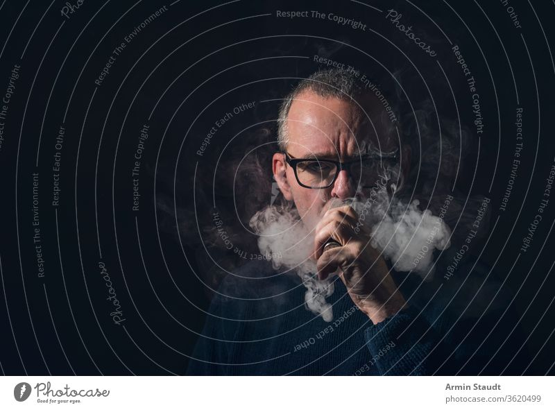 studio portrait of a man with vaporiser and glasses old beard gray vaping smoke cool serious e-cigarette electronic vapes male smoking blowing healthy equipment