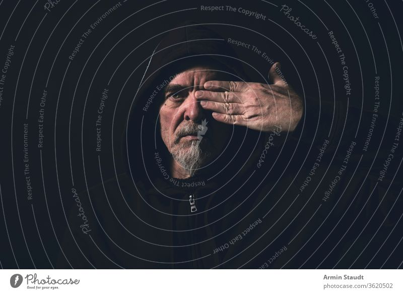 portrait of a man wearing a hoodie, holding one hand in front of an eye blind see cover finger beard gray glass black dark serious danger intensive caucasian