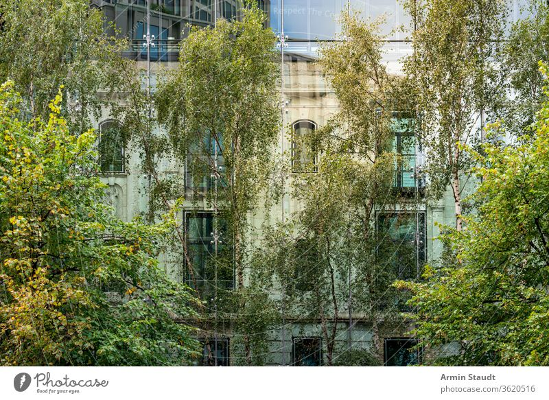 old house behind a modern glass facade with trees in foreground covered architecture nature building two reflection mirroring city urban berlin potzdamer platz