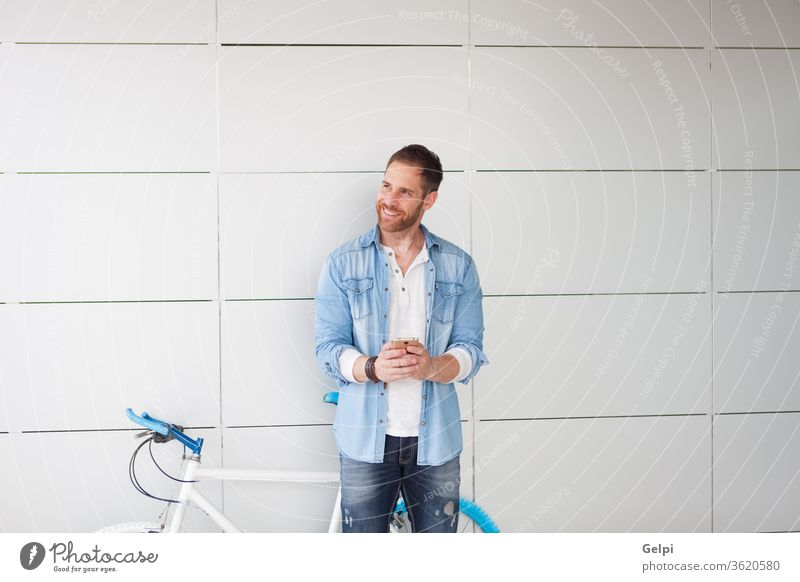 Casual guy next to a vintage bicycle with the mobile phone young man urban lifestyle person male city outdoors hipster bike cell technology street casual