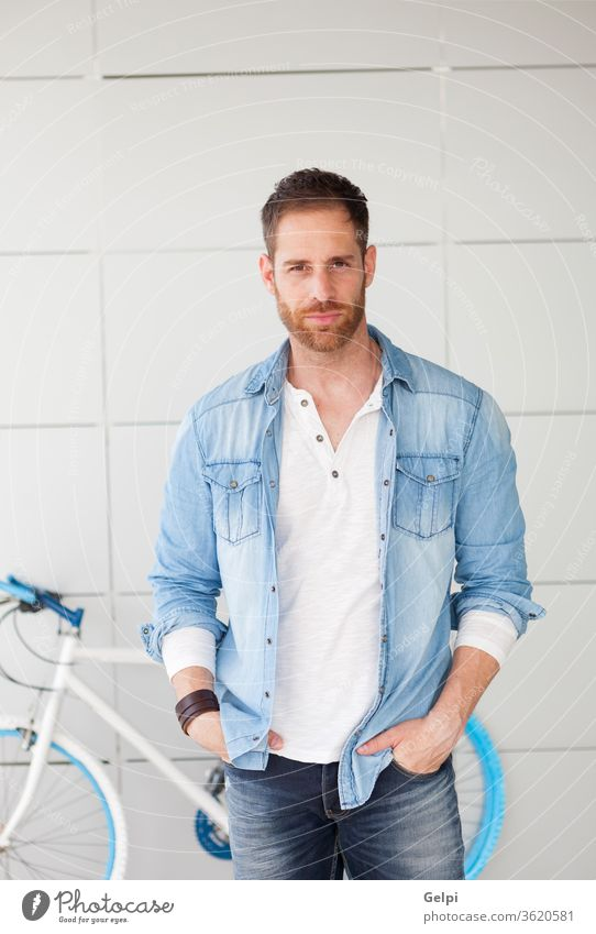 Casual guy next to his bike looking at camera bicycle hipster lifestyle urban young man background handsome male casual blue pensive think fashion person happy