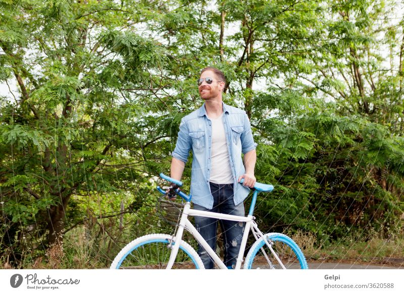 Handsome man enjoying with his bike in the park casual lifestyle male guy young leisure bicycle summer people active adult person urban caucasian outside sport