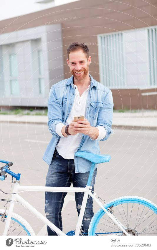 Casual guy next to a vintage bicycle with the mobile wearing denim shirt phone young man urban lifestyle office business businessman person male city outdoors