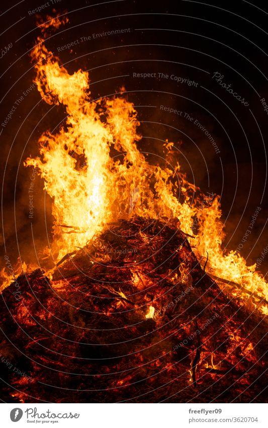 Big bonfire burning in the night heat embers ash resource copy space combustion light light source San Juan spain black background flames orange hot warm danger