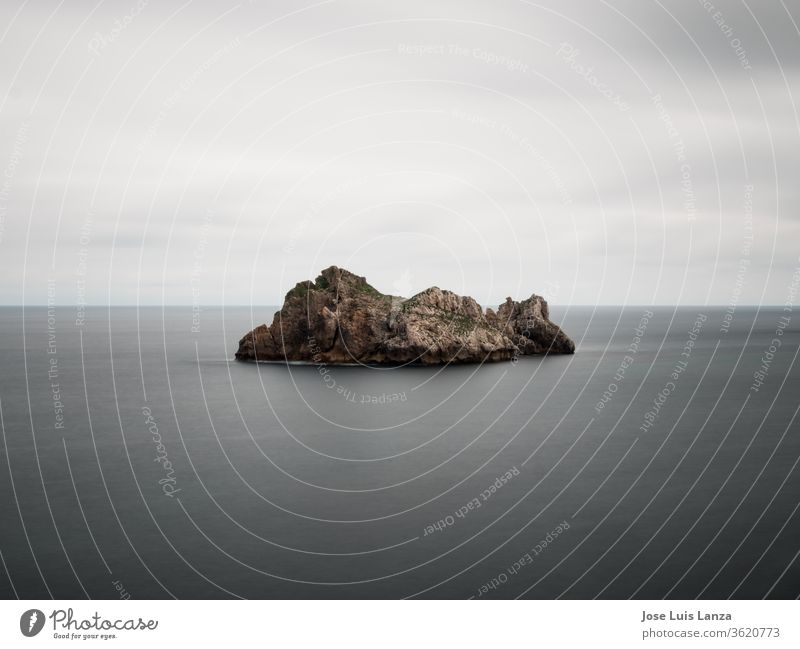 rocky island in the sea minimalist landscape ocean blue seascape Coast Blue travel nature Nature Vacation & Travel cloudscape water peaceful background Moody