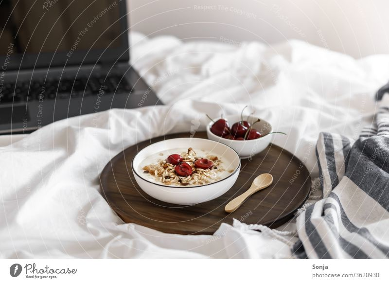 Yoghurt with muesli and cherries on a white duvet and a laptop Cereal Breakfast Bed Bedroom home office fruit Cherry bowls Dessert Oats White Organic Spoon