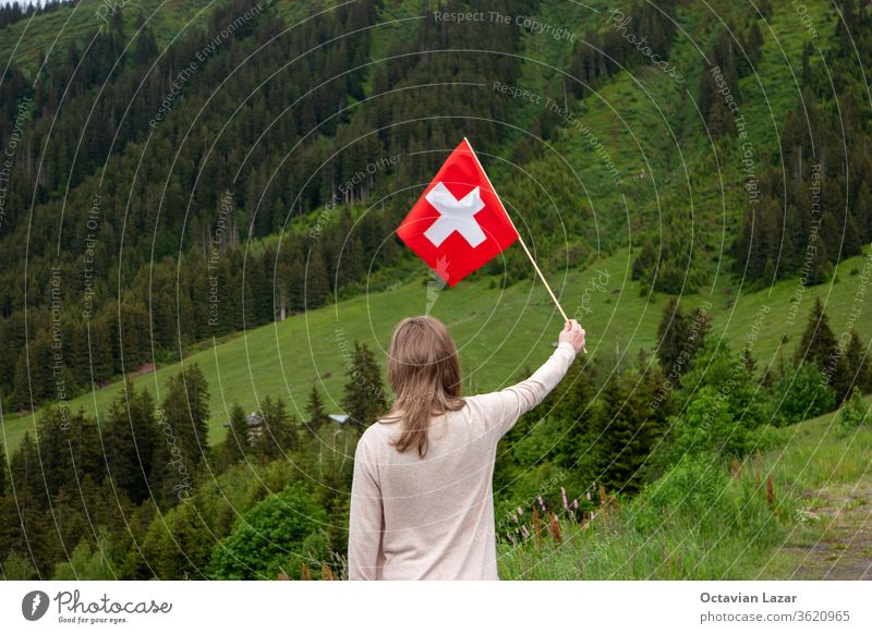 Caucasian blonde girl waving the Swiss national flag with her back to the camera and the Alps in the background europe switzerland day august swiss young female