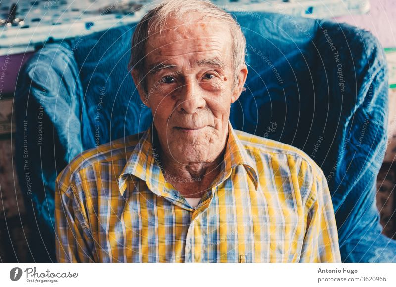 portrait of a smiling old man with health problems sitting on his couch. confused plaid shirt person patient one person photography senior adult bed elderly