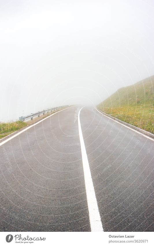 Asphalt paved mountain road covered in fog no cars or people foggy mist street asphalt caution low visibility visibility concept danger light oberalppass