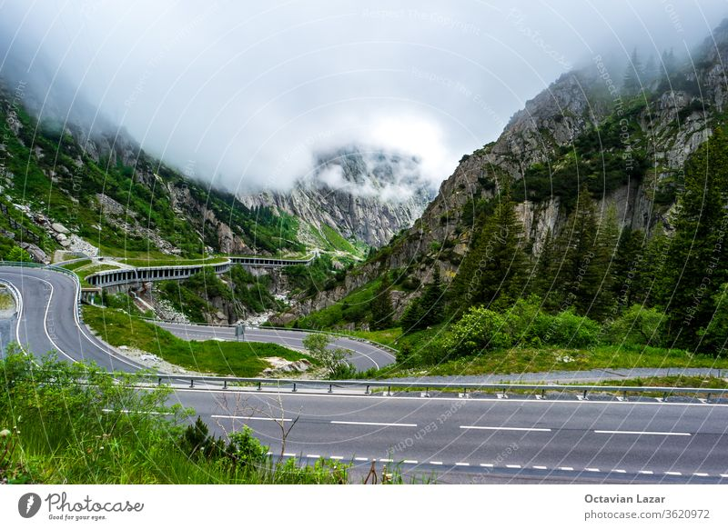 High altitude serpentine mountain pass in the Swiss alps Oberalppass top view cloudy summer day national landscape turn route road trip stone wilderness curve