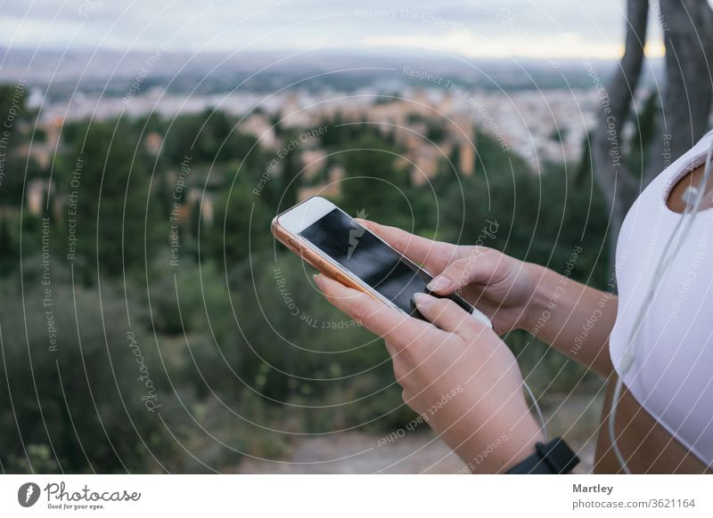 Hands of a young girl using the phone in nature after exercising. Crop an irecognizable woman using the mobile tracking app while exercising outdoors activity