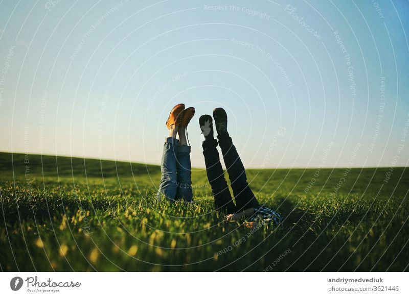 View of a man's and woman's legs sticking up out of tall green grass on summer day.selective focus. nois. people boyfriend girlfriend couple barefoot caucasian