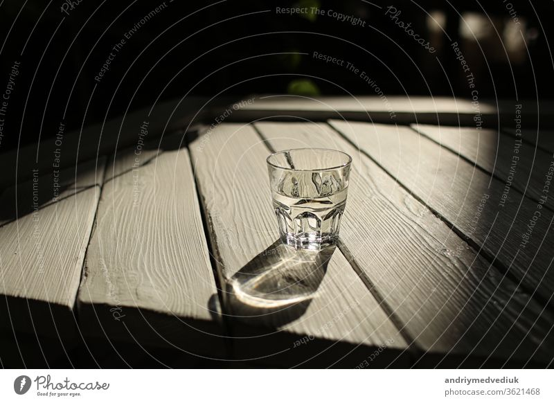 a glass of water on a white table with rays of the sun with nature background clear light wood fresh clean freshness drink pure transparent summer wooden shadow