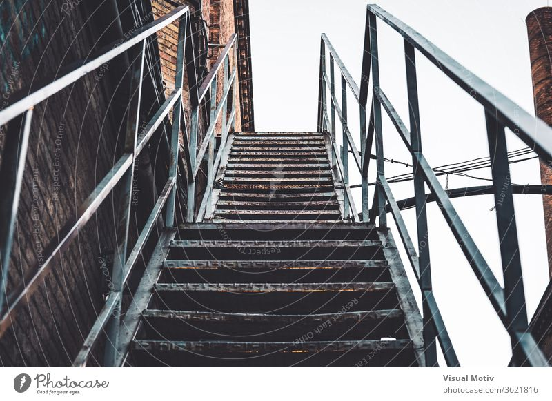 Exterior rusty stairs of an old abandoned textile factory building stairway shabby metallic brick exterior weathered aged structure industrial construction