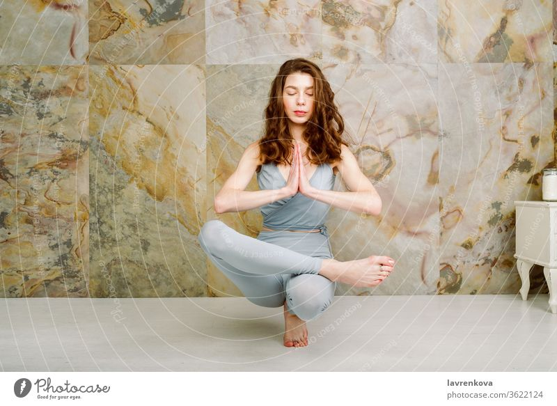Young female practicing Toe Stand (Padangusthasana) Pose indoors, selective focus yoga workout sport active woman yogini athletic slim skinny balance young