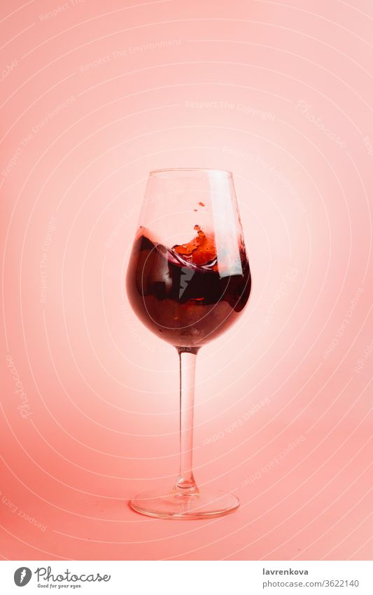 Red wine splash in a glass, dynamic picture, selective focus. liquor pouring droplet liquid winery red beverage drink celebration alcohol pink motion drops