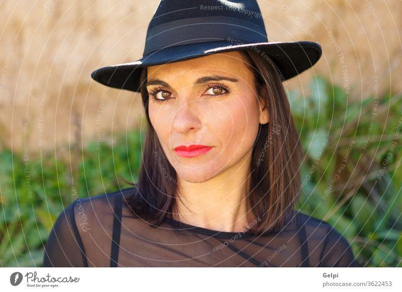 Attractive mature woman with black hat autumn female beautiful people fall adult lifestyle beauty portrait outside nature fashion landscape walking lady elegant