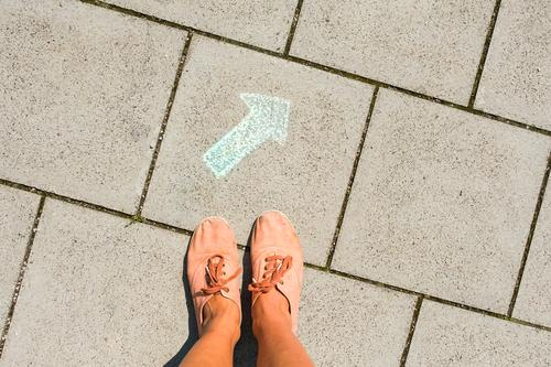Feet stand in front of a green arrow painted on the floor with chalk. Signpost, direction, decision support. Road marking Direction Decide off Correct Arrow