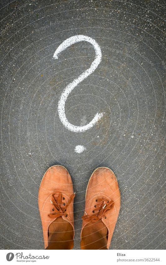 Feet stand in front of a question mark painted on the floor with chalk. Question, perplexity, indecision. Decide Perplexed Question mark disorientation