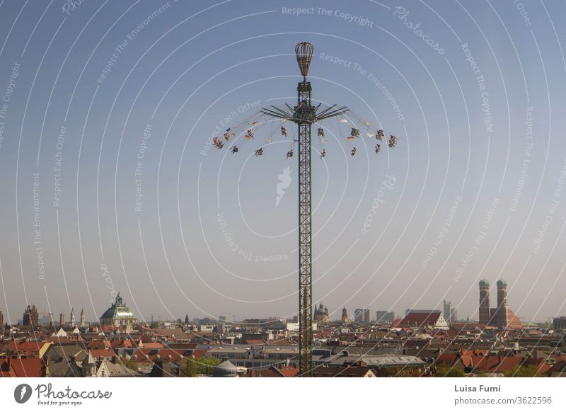 MUNICH, GERMANY -  Panoramic view of Munich and a drop tower, from the spring festival at the Theresienwiese amusement park carousel ride people cityscape