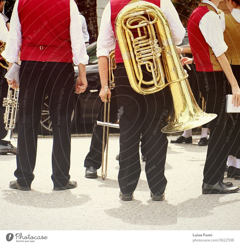 Brass band musicians in Bavarian costume with their instruments  attending a traditional parade brass festival Germany Bavarian town Munich folklore Tracht