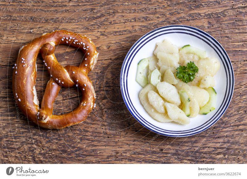 Bavarian potato salad on wood Fresh pretzel Pretzel supervision Eating green Dressing Vegetable Onion Lettuce Meal Dinner White scatterbrained German spices