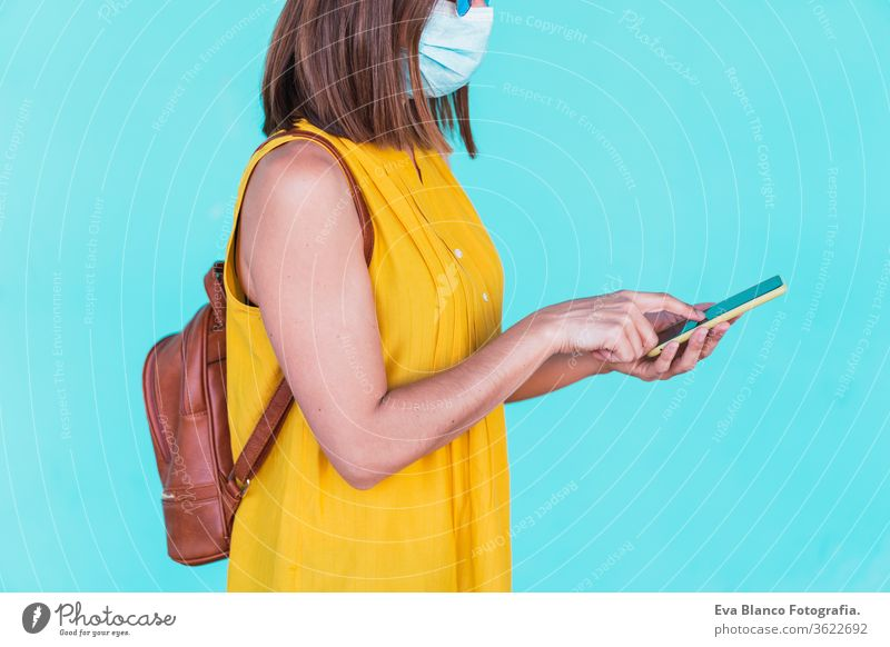 Portrait of a young woman in front of a turquoise background with a protective mask. With mobile phone. Summertime and coronavirus concept Technology Woman