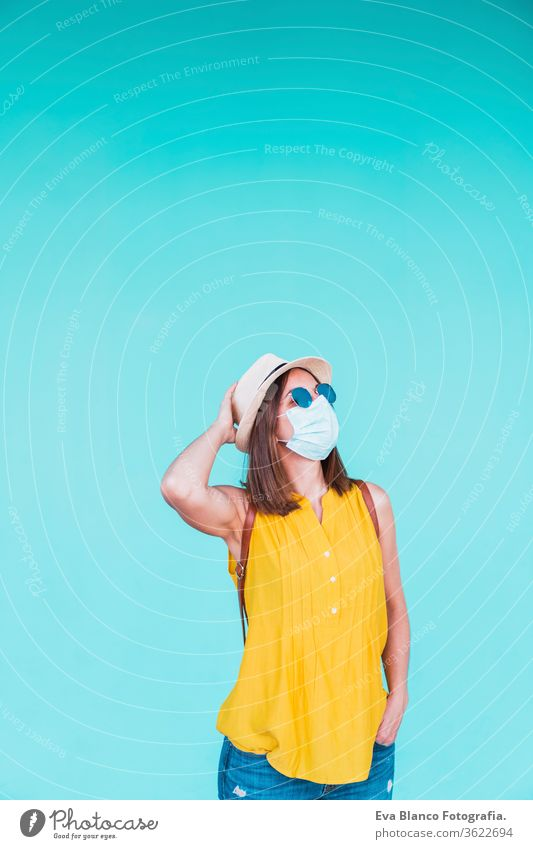 portrait of young woman outdoors over turquoise background wearing protective mask. Summer time and corona virus concept epidemic attitude saying infectious