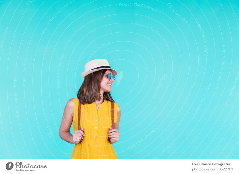 portrait of happy young woman outdoors over turquoise background. Summer time mobile phone summer sunglasses yellow hat backpack city urban lifestyle smiling