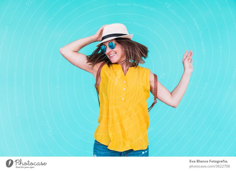 portrait of young woman dancing and jumping outdoors over turquoise background. Summer time mobile phone summer sunglasses yellow hat backpack city urban