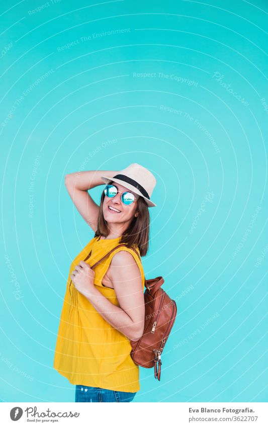 portrait of young woman outdoors over turquoise background. Summer time mobile phone summer sunglasses yellow hat backpack city urban lifestyle happy smiling