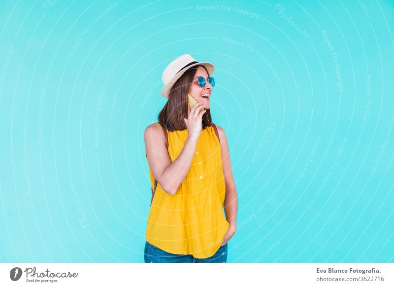young woman using mobile phone outdoors over turquoise background. Summer time summer sunglasses yellow hat backpack city urban lifestyle happy smiling girls