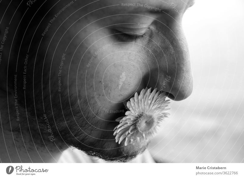 portrait of man with flower in mouth to show concept of kindness, power of words and vulnerability humanity black and white portrait kindness concept kind words