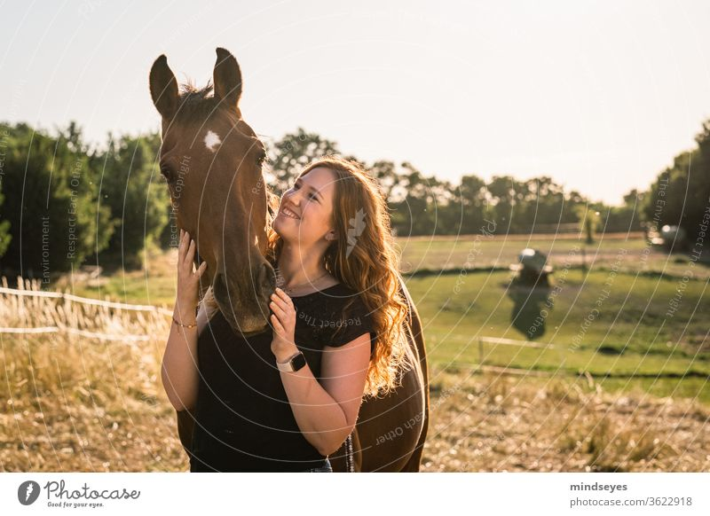 Young woman with horse in the meadow golden light youthful Woman red hair Summer Lifestyle Face people portrait girl Easygoing already Horse Nature Country life