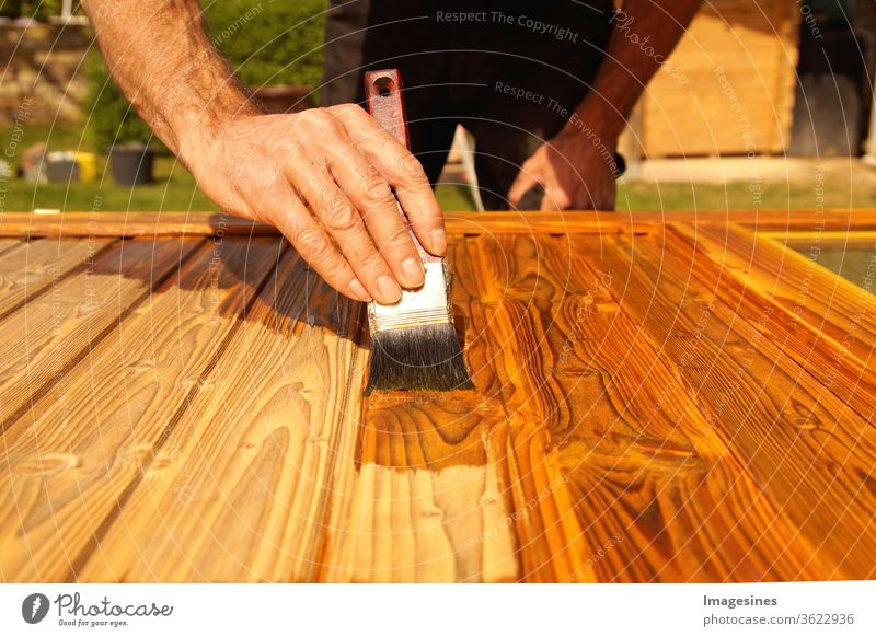 Glaze. Woodwork, painting wood. Hand of the craftsman painting a wooden door. Concept of renovation work, carpentry and woodwork. painter, painting wooden surface, wood preservation