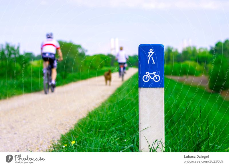 : Cicycle path along the Vistula River in Warsaw, Poland with cyclists visible in the background on a sunny summer day. action active activities bicycle