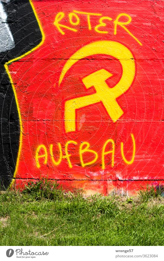 Graffiti Hammer and sickle with yellow paint sprayed on a red background on a wall and completed with the words red construction hammer and sickle yellow color