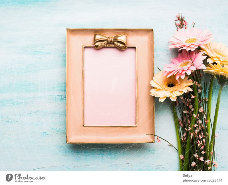 Beautiful flowers and pink frame on pastel green woman day card blank gift greeting floral flat lay spring holiday festive background invitation beautiful