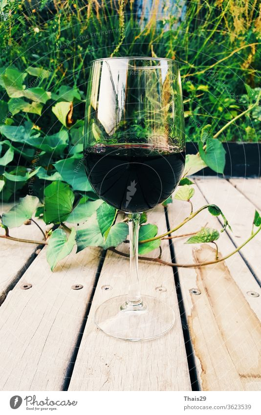 glass of red wine on wooden background outdoor garden alcohol alcoholic bar barrel beverage bottle celebration closeup culture drink food grape italian leaf