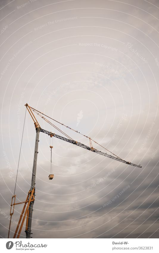 a crane on a building site Crane Sky Clouds great huge Tall Construction site somber Thunder and lightning Storm Gray construction stop Build standstill Above
