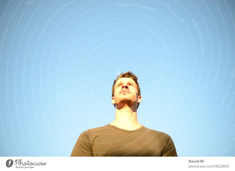 Man looks up into the blue sky and has a questionable expression Upward ponder Think think thoughts Sky Blue background Neutral Background Neutral background