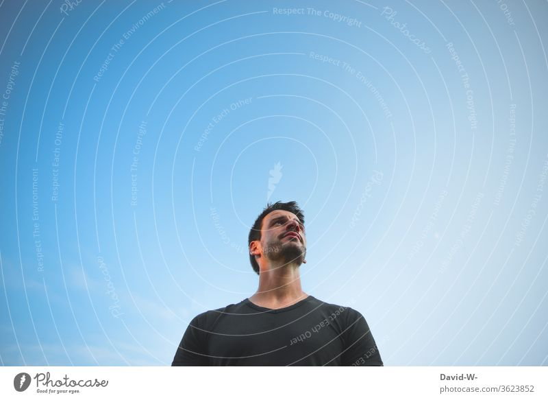 Man looks thoughtfully into the sky - looking up Upward ponder Think think thoughts Sky Blue background Neutral Background Neutral background Copy Space top