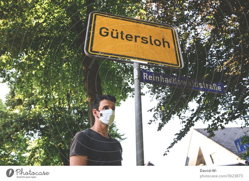 Man with breathing mask in Gütersloh - place-name sign - Corona / covid19 Rheda-Wiedenbrück Oelde cordon keep sb./sth. apart gap Safety covid-19 Tönnies