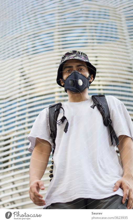 A Young Man outdoors in a protective face mask to prevent Corona virus infection wearing a floral printed bucket cap and a bag pack during Global pandemic.