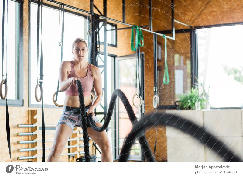 Young woman in the gym training crossfit on the ropes beautiful strength tough equipment sports sporty endurance fitness attractive alternating pulling energy
