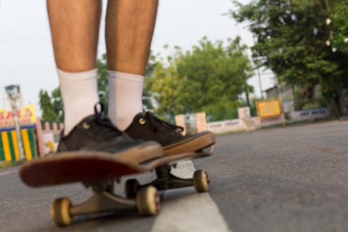 Blurred closeup shot of someone's feet who is cruising on a skateboard on an empty  road. skateboarding recreation lifestyle empty roads summer outdoor lockdown
