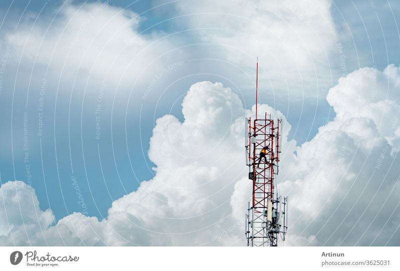 Telecommunication tower with blue sky and white clouds. Worker installed 5g equipment on telecommunication tower.Communication technology. Telecommunication industry. Mobile or telecom 5g network.